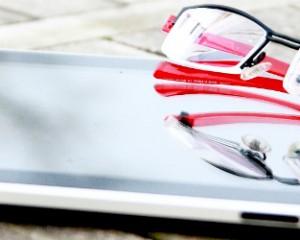 ipad en bril op houten tafel
