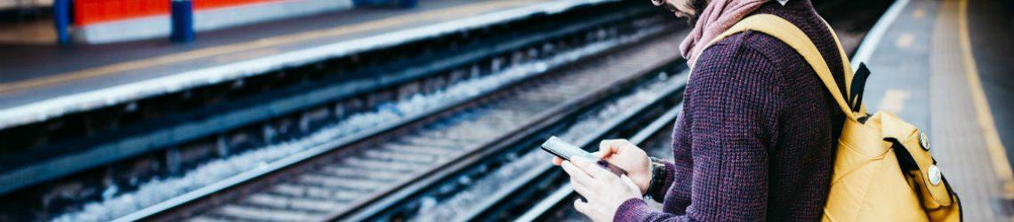 Man bij treinspoor op mobiel