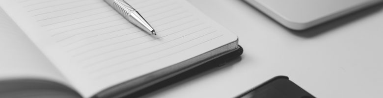 notitieboekje met pen, telefoon en laptop