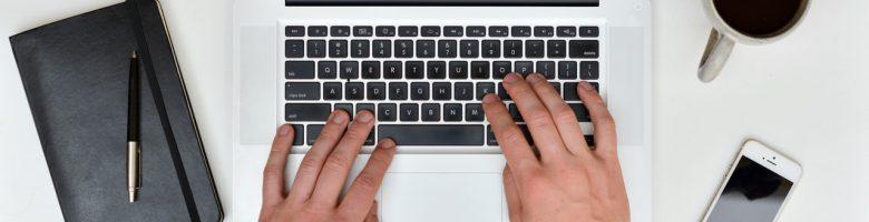 Handen typen op een laptop. Op tafel staan voorwerpen zoals een telefoon en een kop koffie.
