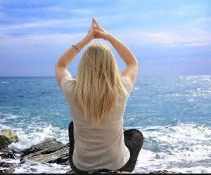 Vrouw zittend in yogahouding aan de zee